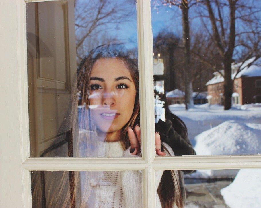 Mulher olhando pela janela o lado de fora