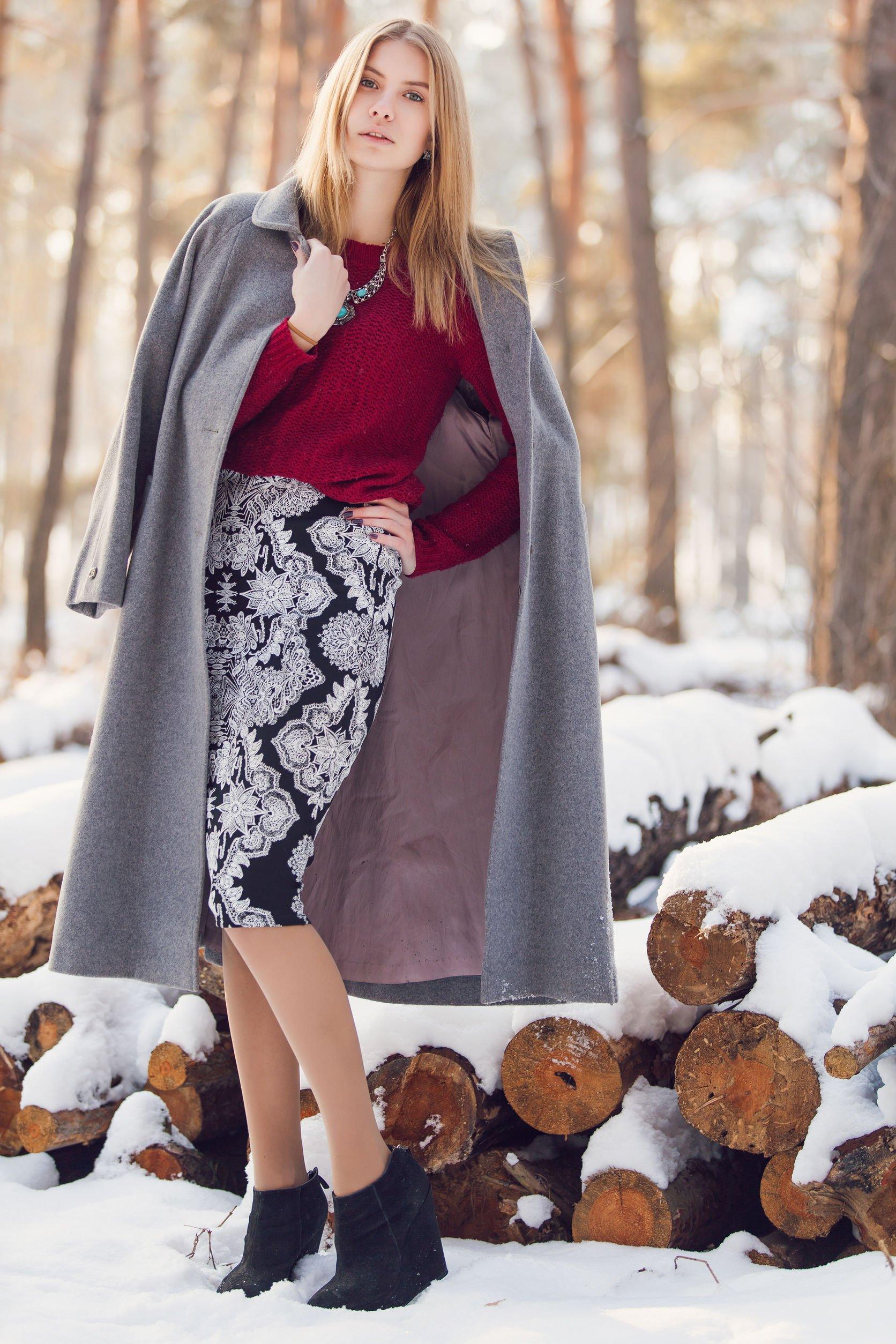 Mulher com roupas de sociais de frio ao lado de troncos de árvore cobertos de neve