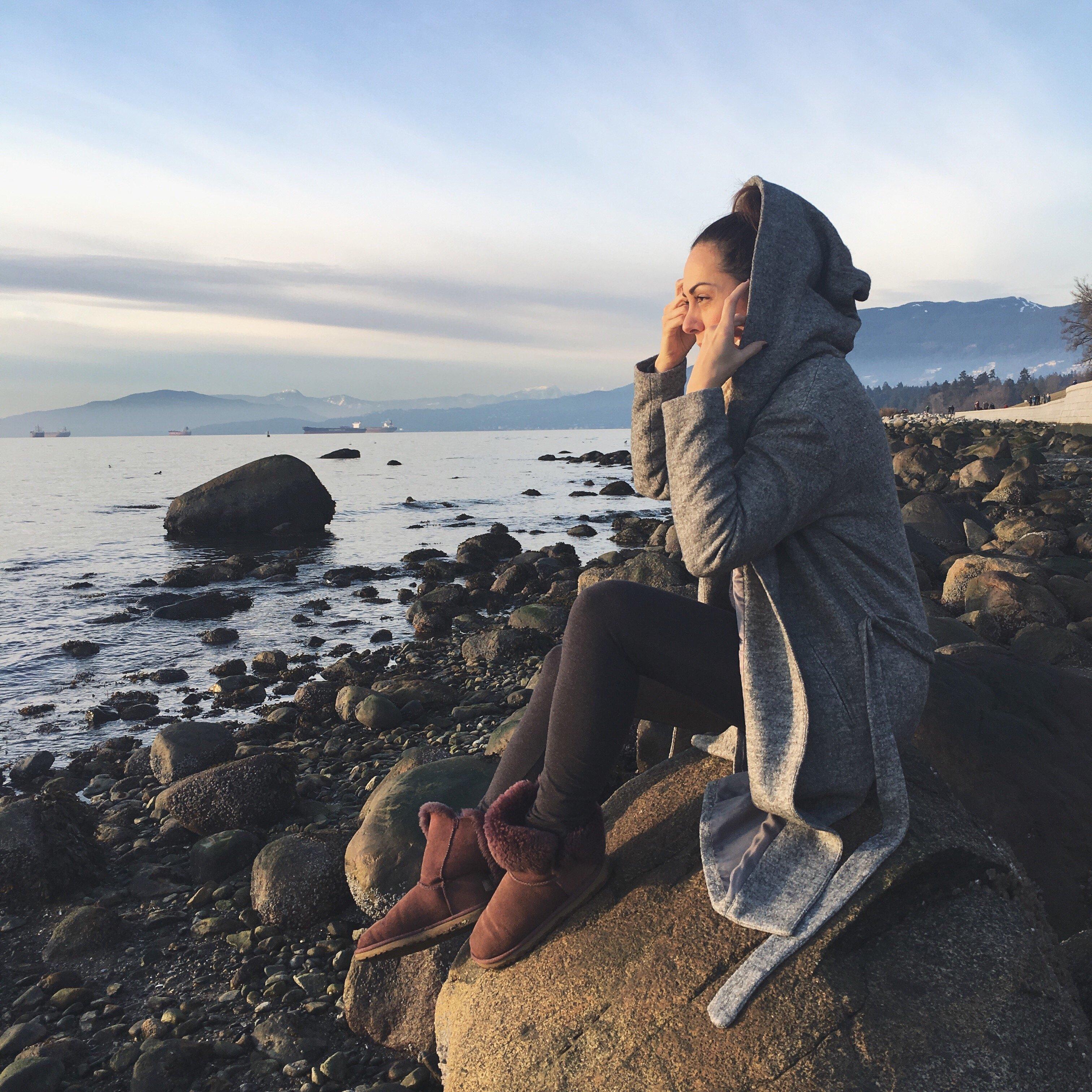 Mulher sentada em uma rocha na praia segurando a touca do sobretudo