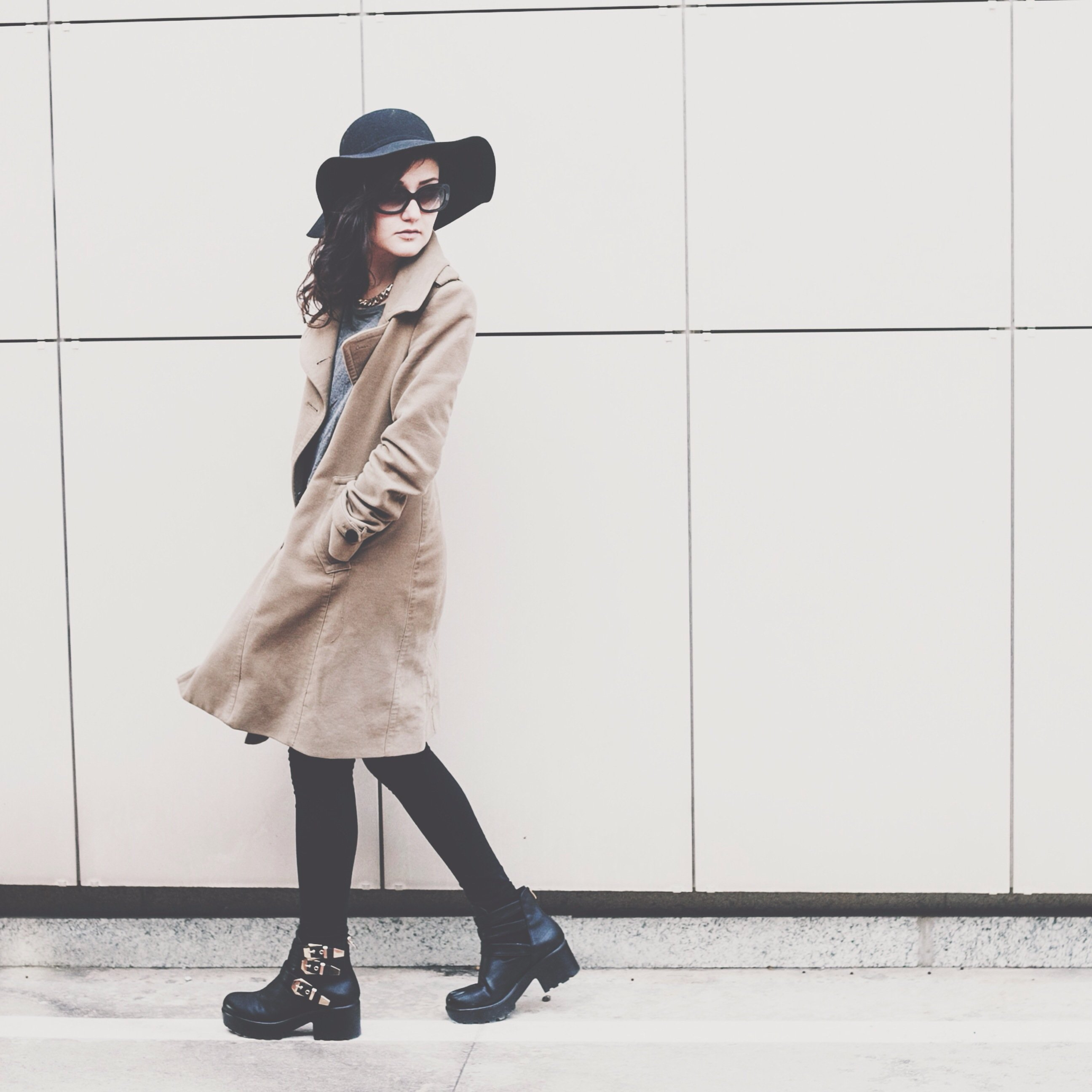 Mulher andando na rua olhando para trás usando sobretudo e botas