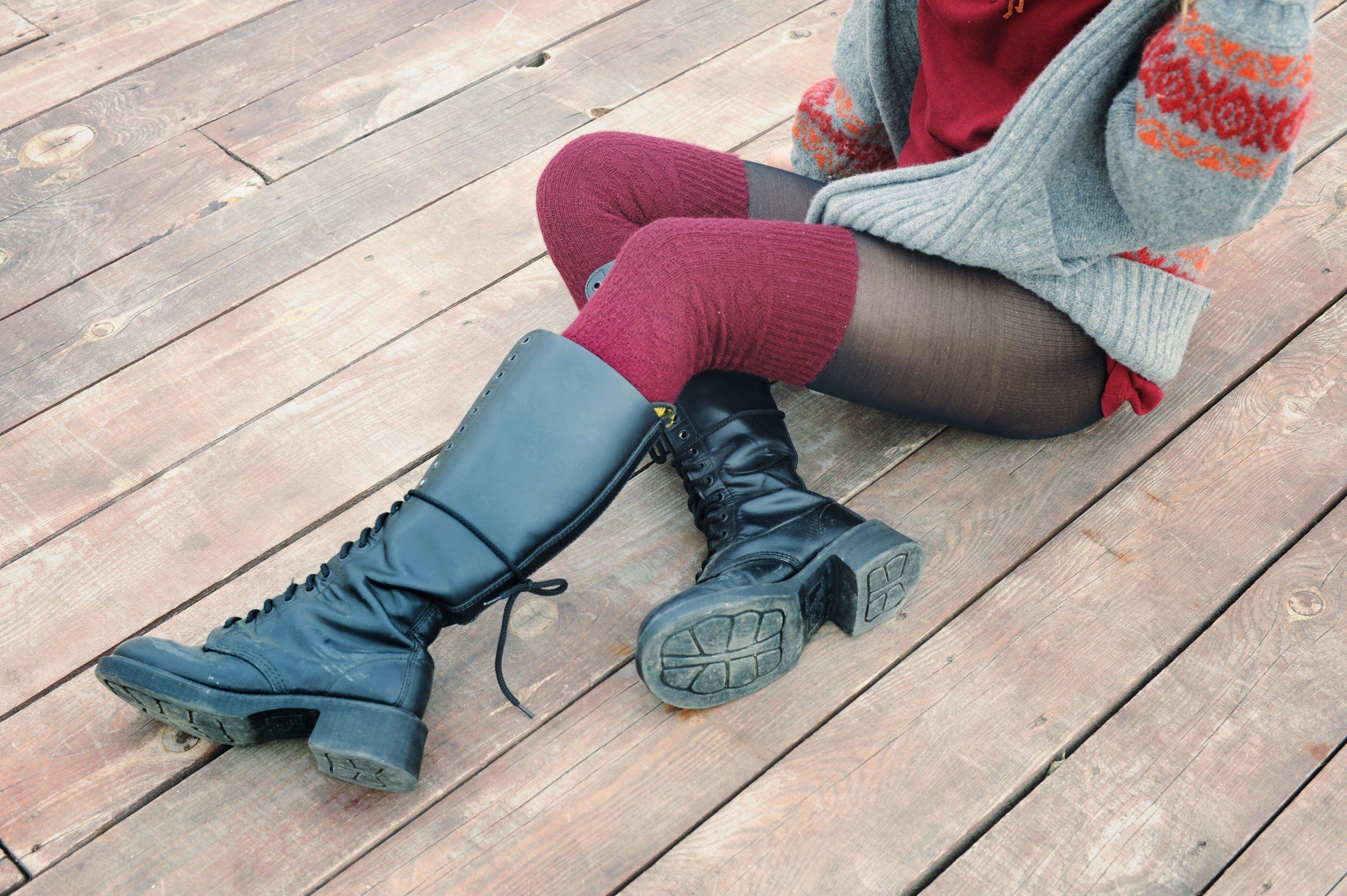 Mulher sentada no chão usando botas e meias longas