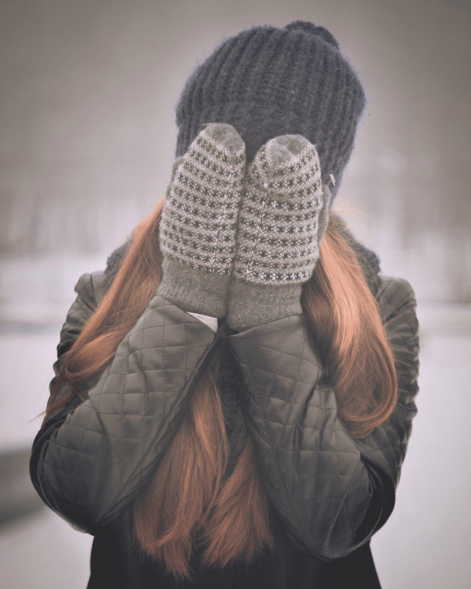 Mulher usando touca e luvas cobrindo o rosto