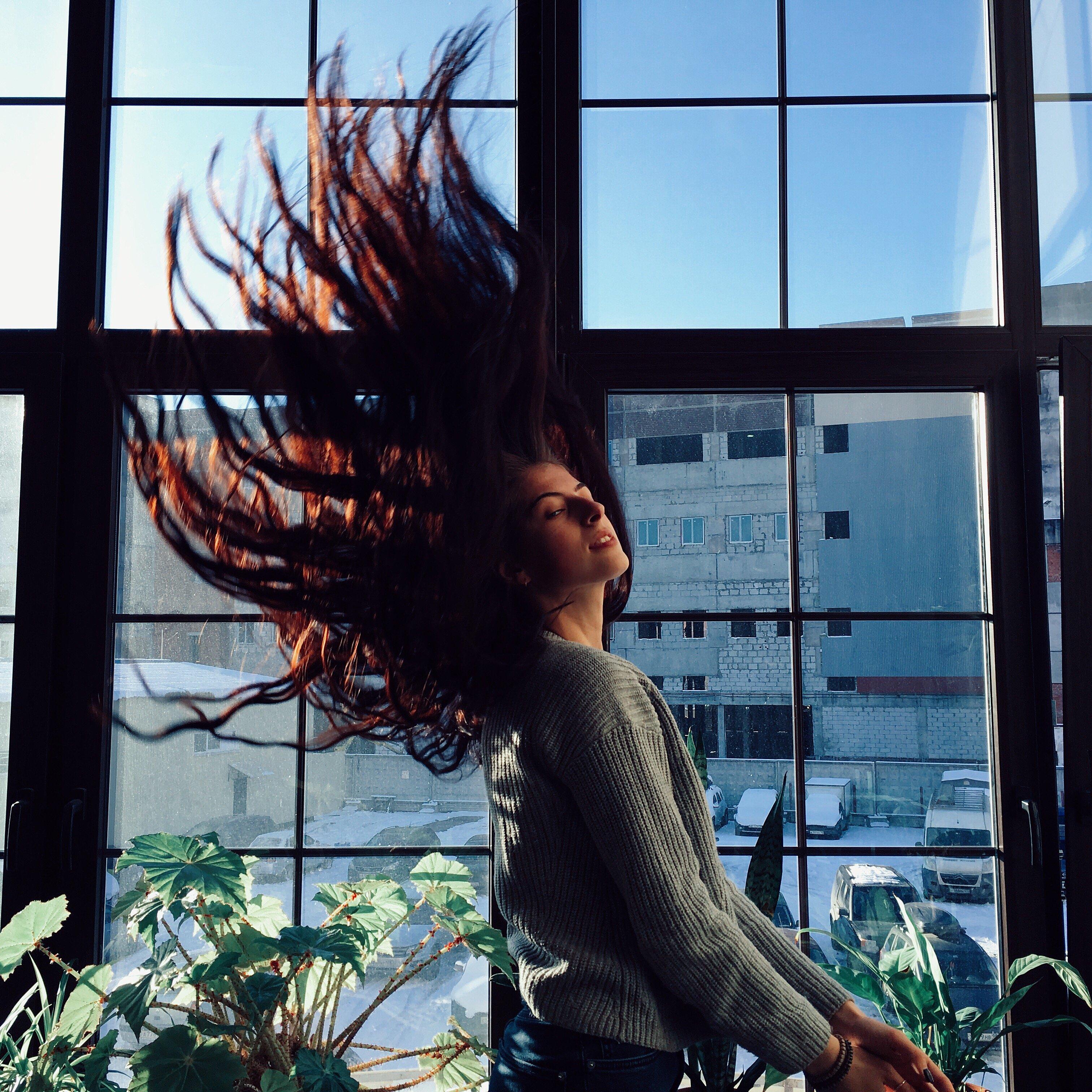 Mulher jogando cabelo para o alto de olhos fechados