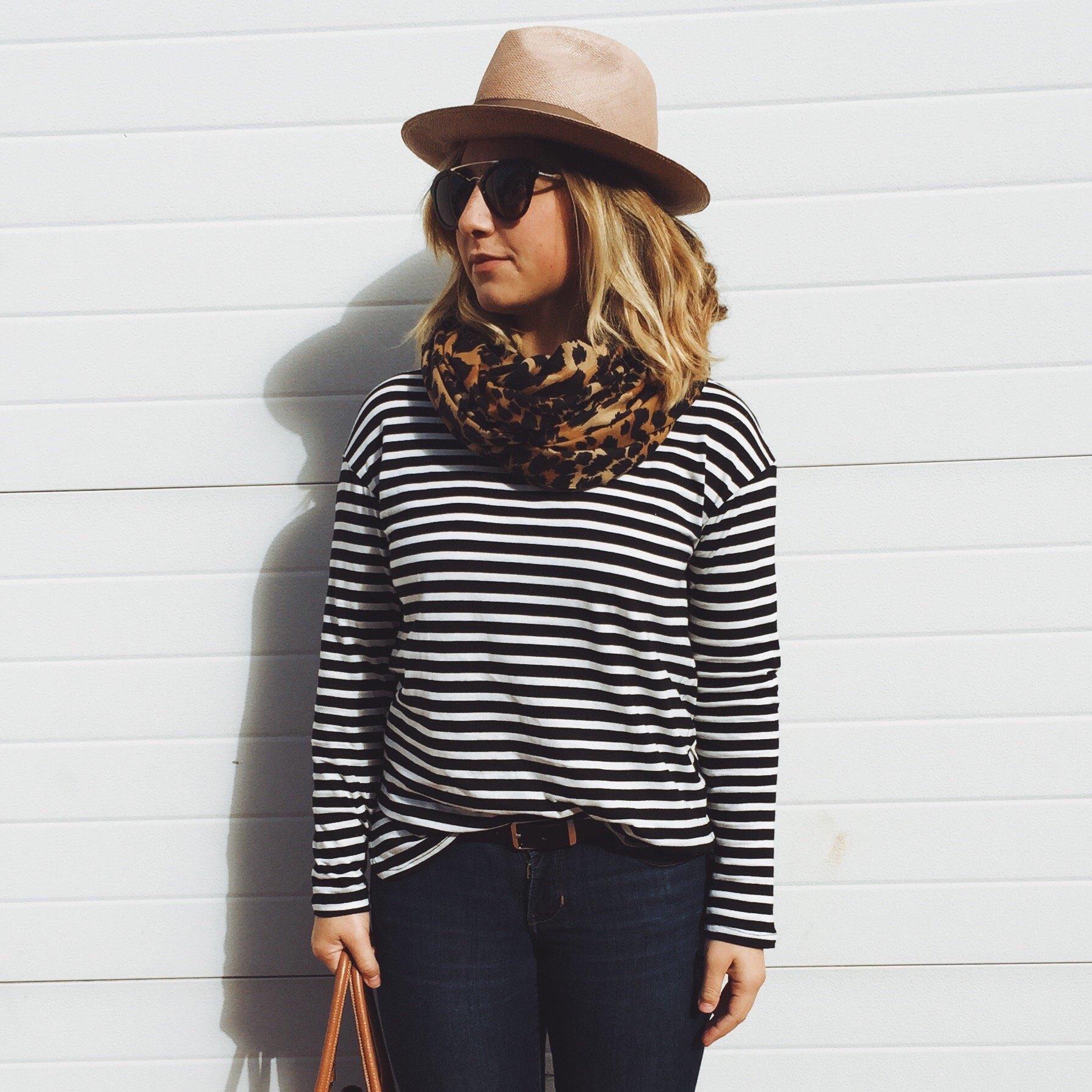 Mulher usando óculos de sol, cachecol e chapéu encostada na parede