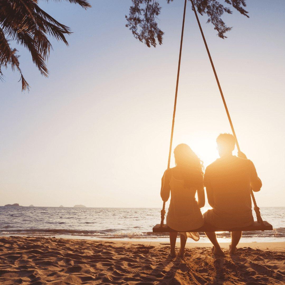 Silhueta de casal sentados no balanço da praia