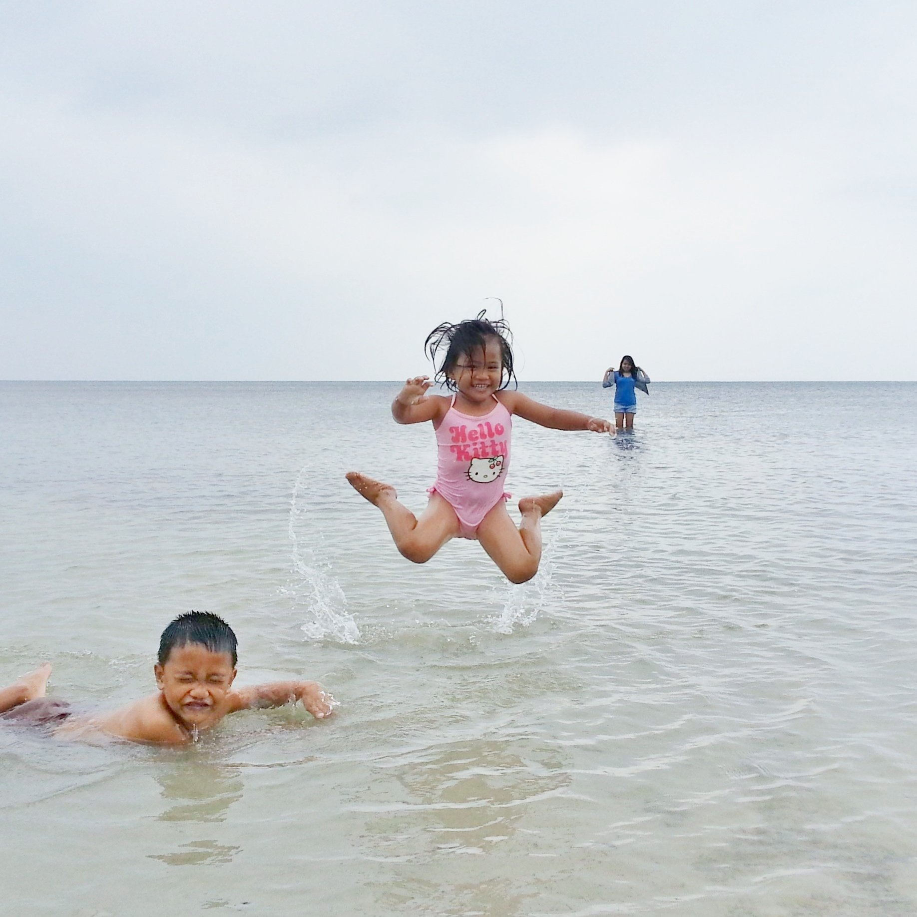 Criança pulando na água da praia sorrindo