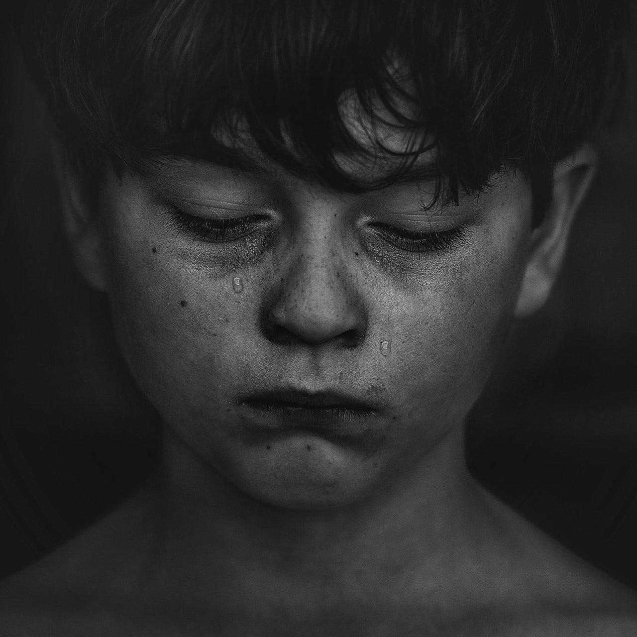 Criança chorando olhando para baixp