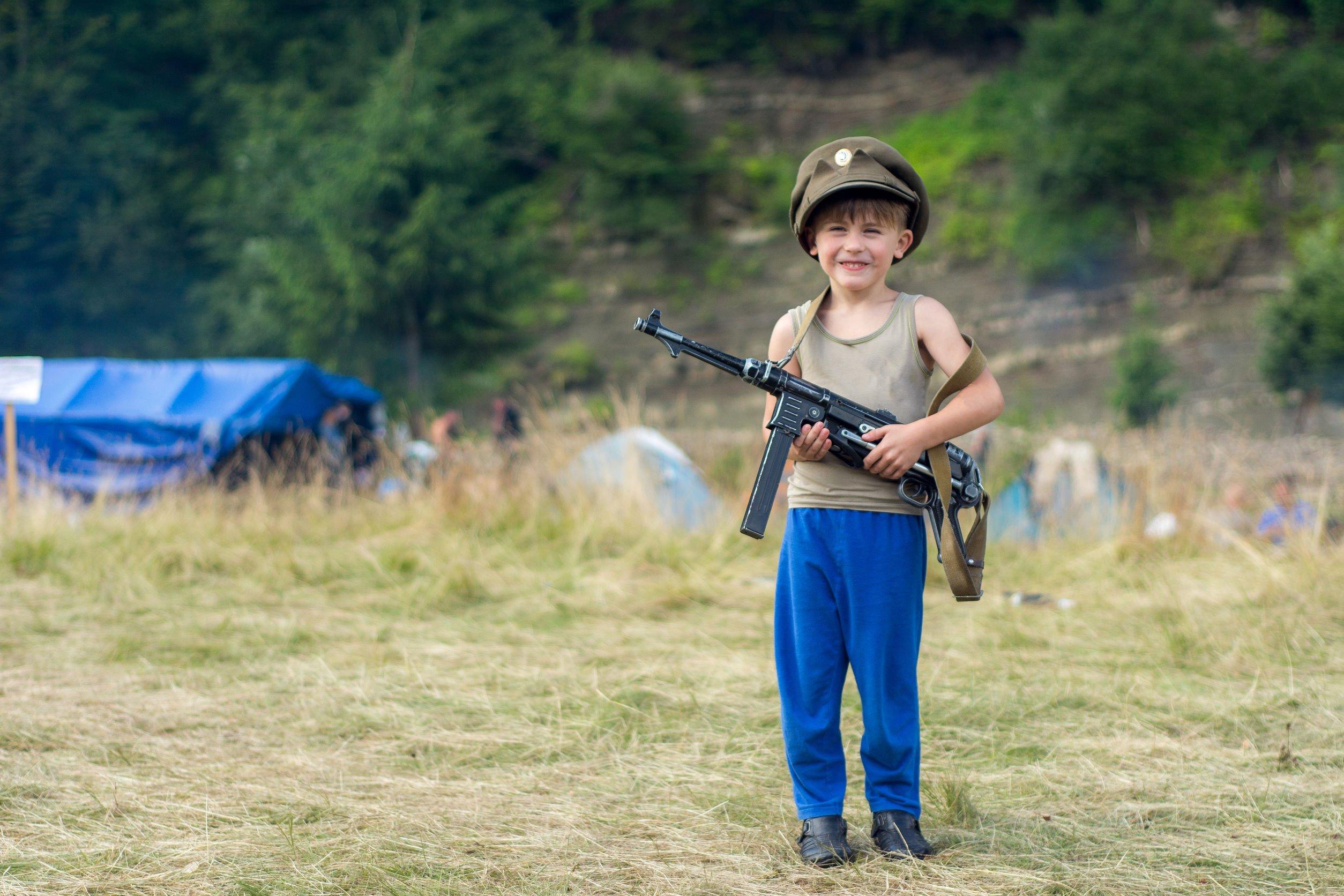 Criança segurando uma arma e sorrindo