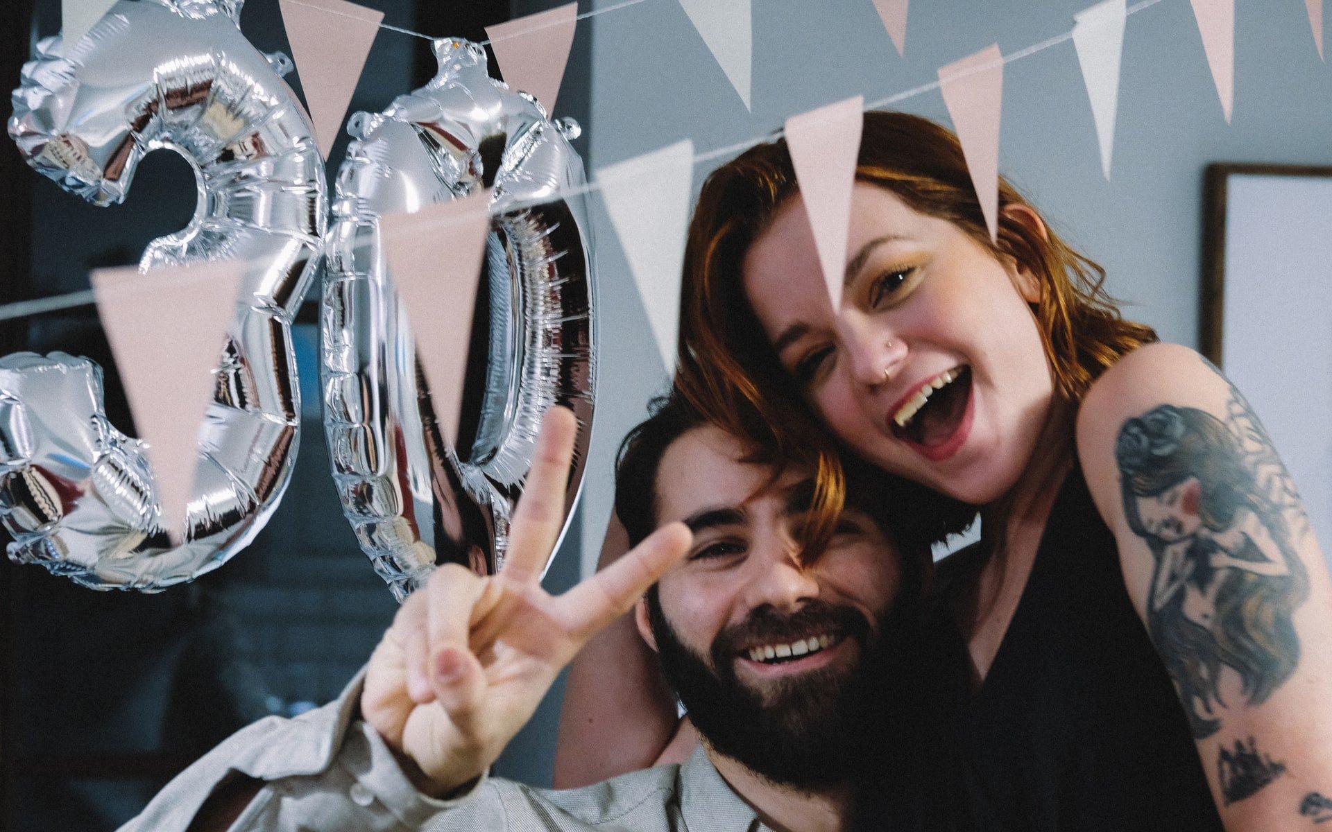 Homem e mulher brancos abraçados durante uma festa de aniversário.