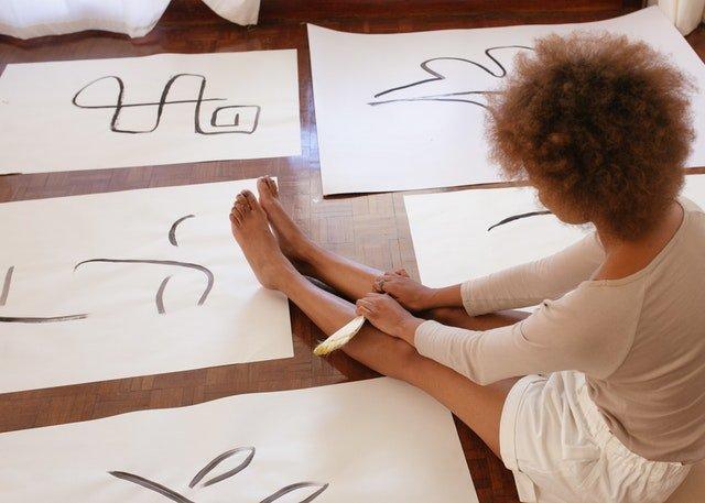 Mulher sentada em meio a desenhos.