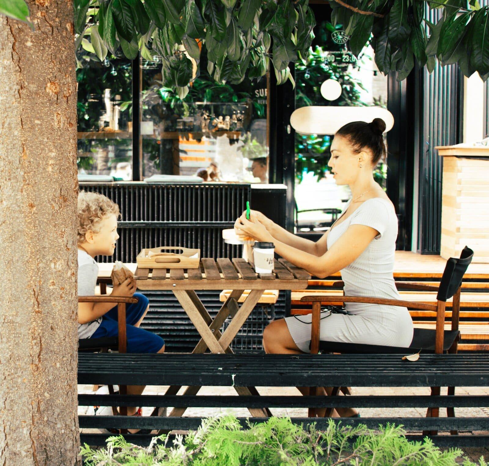 Mulher e uma criança sentados em uma mesa de madeira tomando café.