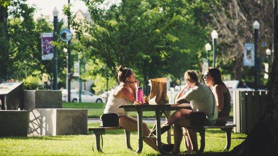 Três mulheres sentadas na mesa da praça