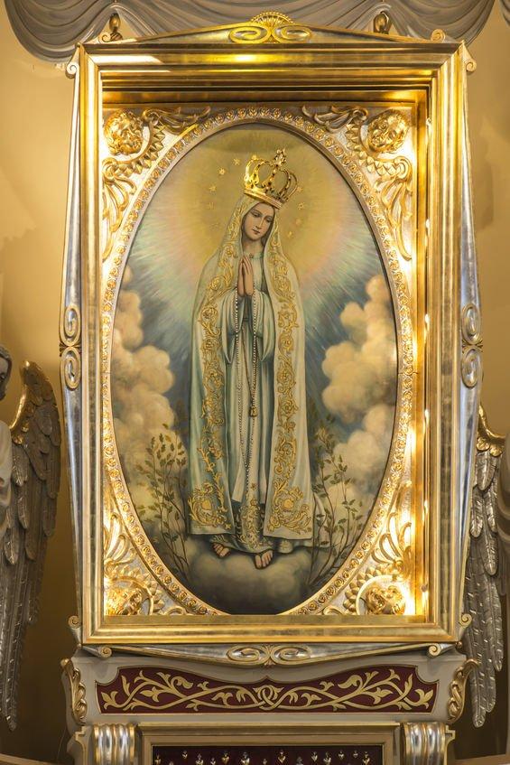 Imagem de Nossa Senhora, com moldura de ouro, no altar de uma igreja.