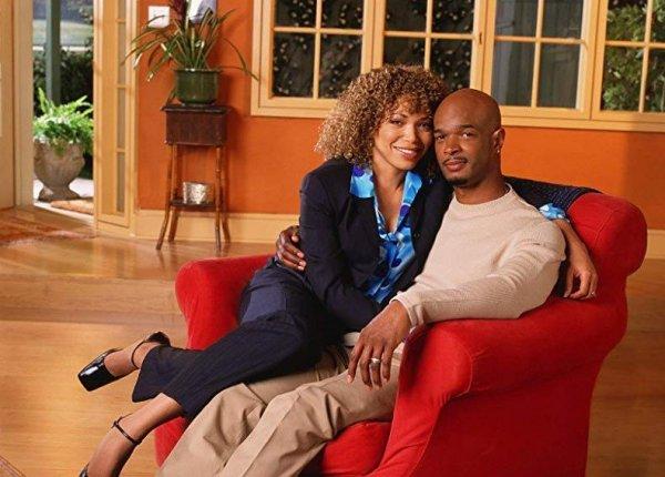 Casal protagonista da série, Michael e Janet, sentados em uma poltrona, abraçados.