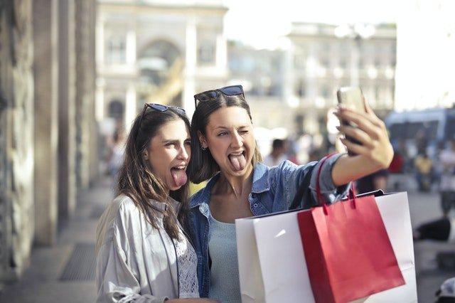 Duas amigas rindo enquanto tiram uma selfie