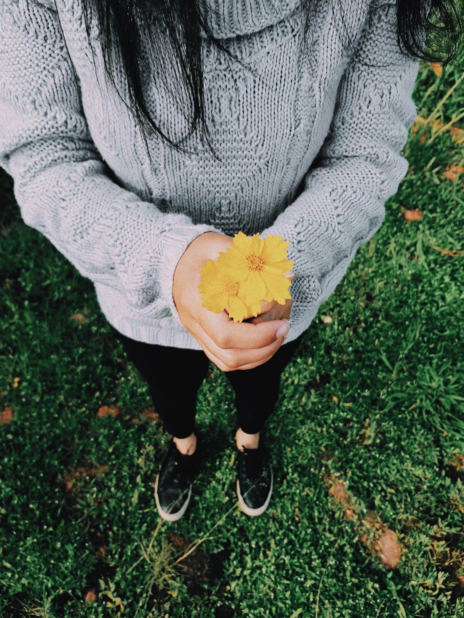 Mulher segurando flor amarela