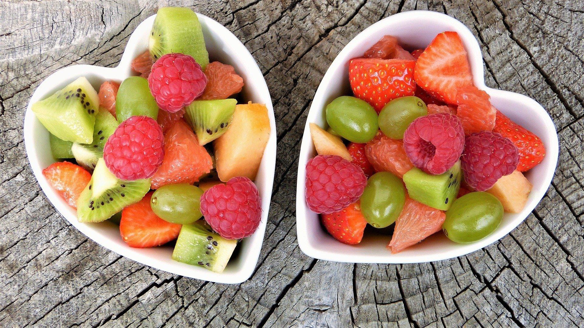 Dois potinhos em formato de coração com frutas em cima de uma mesa de madeira
