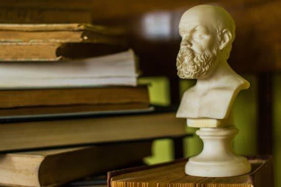 Estátua pequena de pensador ao lado de alguns livros
