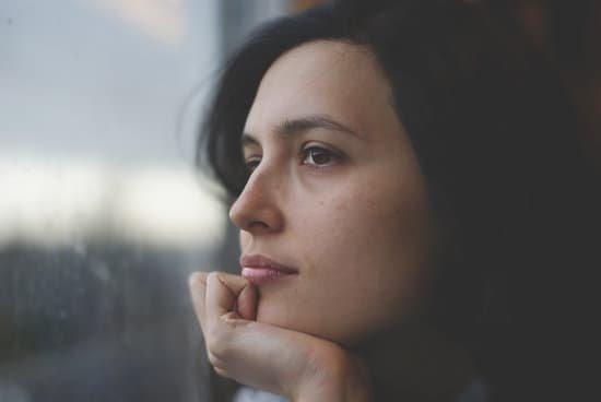 Mulher apoiando seu queixo na mão olhando para a janela pensativa