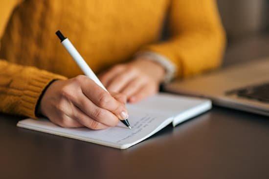Mulher escrevendo em um caderno com caneta