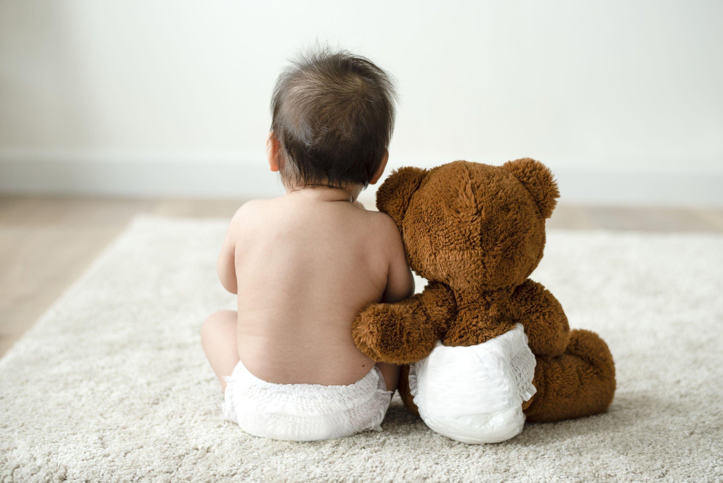 Bebê sentado no tapete ao lado de um ursinho de pelúcia