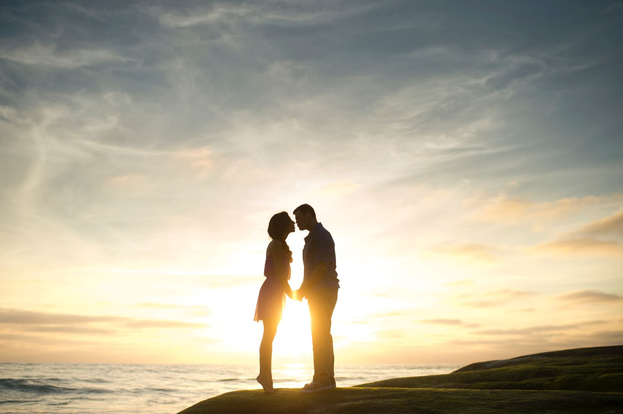 Casal se beijando em praia e Sol ao fundo