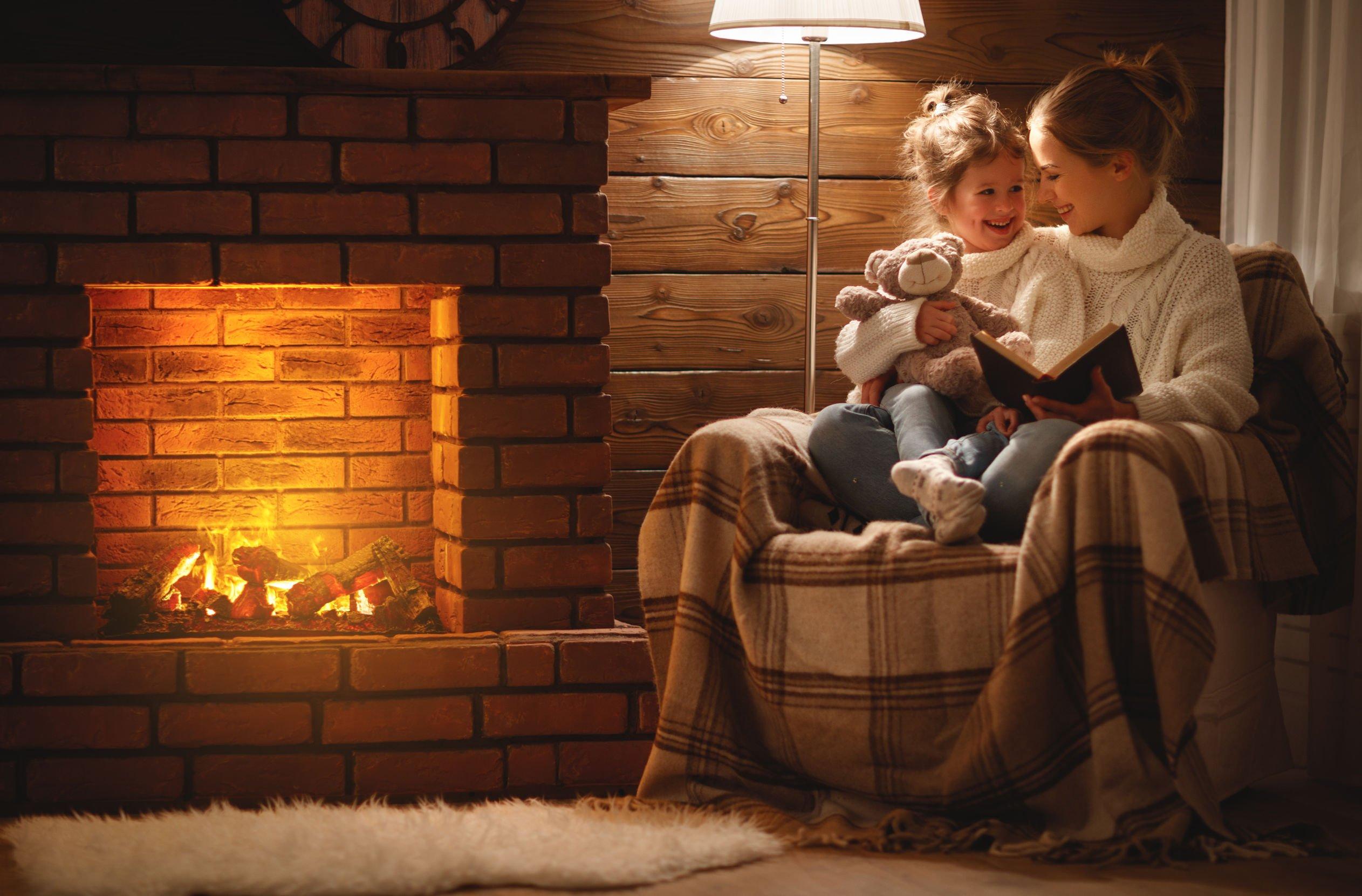 Mãe e filha sentadas em uma poltrona ao lado de uma lareira