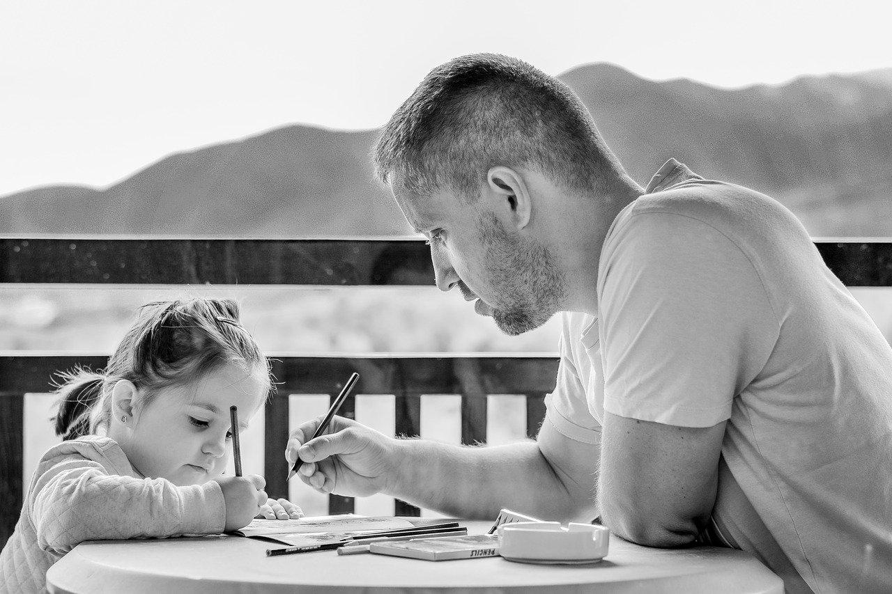 Homem desenhando em uma mesa com uma criança em sua frente
