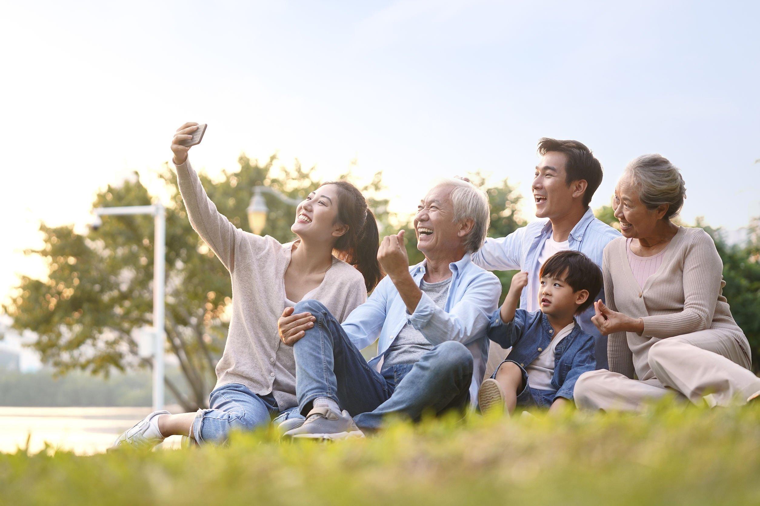 Família sentada em um gramado tirando foto