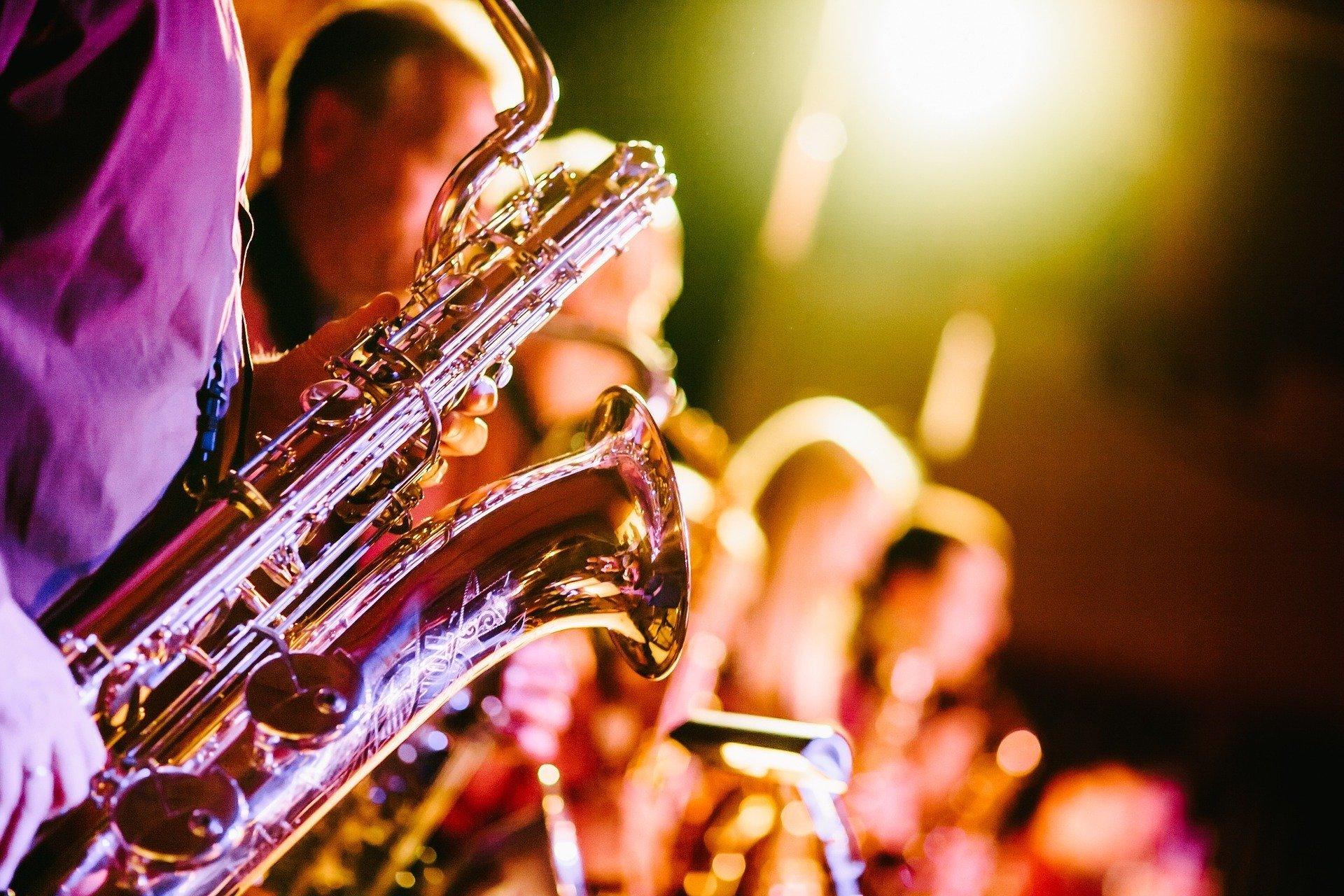 Orquestra desfocada, dando destaque a pessoa com saxofone