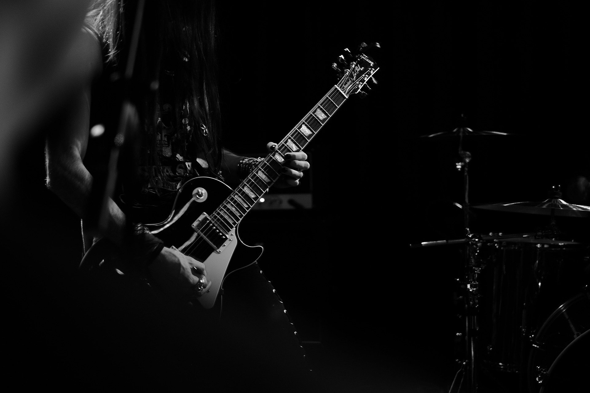 Foto preta e branca de pessoa tocando guitarra