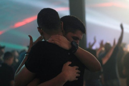 Dois homens se abraçando, em uma festa