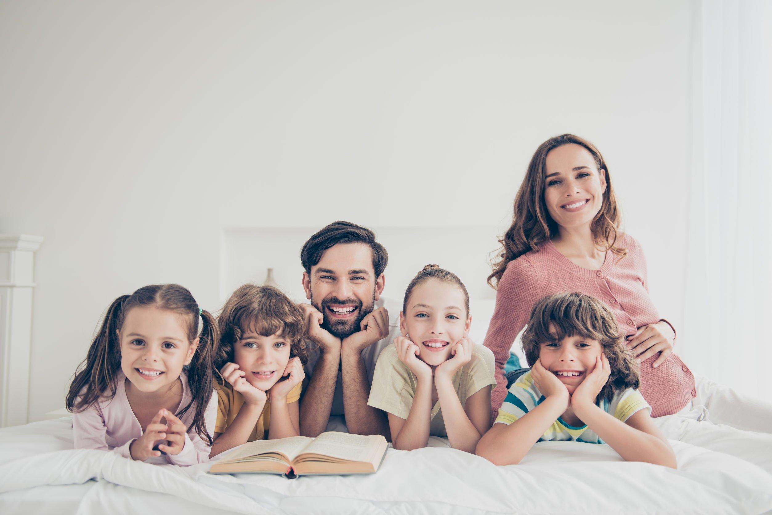 Imagem de família feliz deita em uma cama