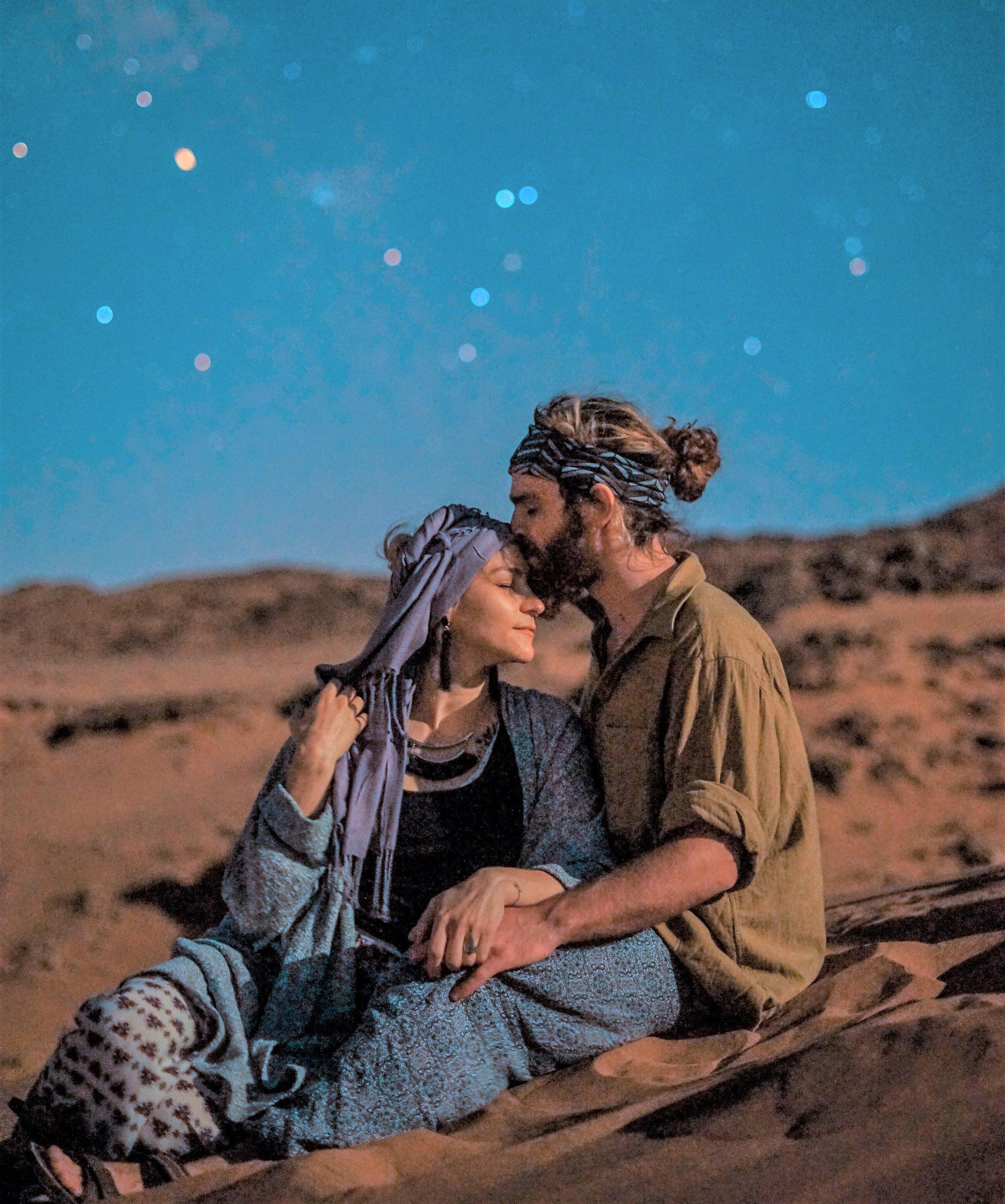 Homem beijando testa da mulher, sentados na areia com fundo estrelado
