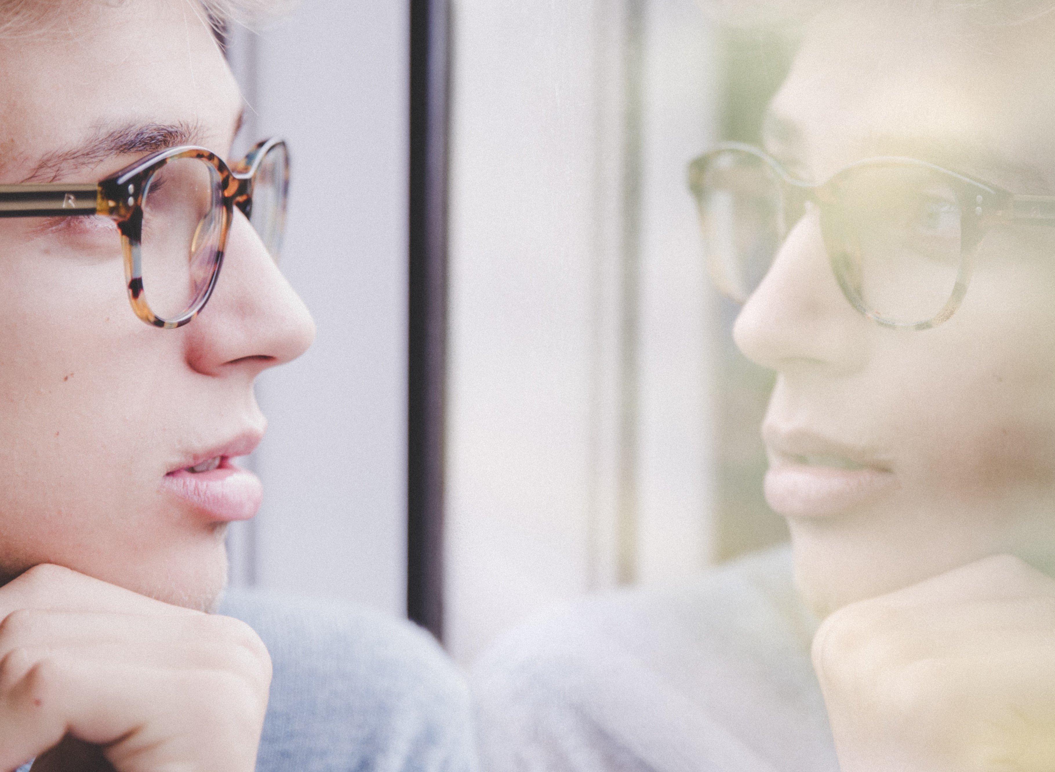 Homem olhando seu reflexo no espelho