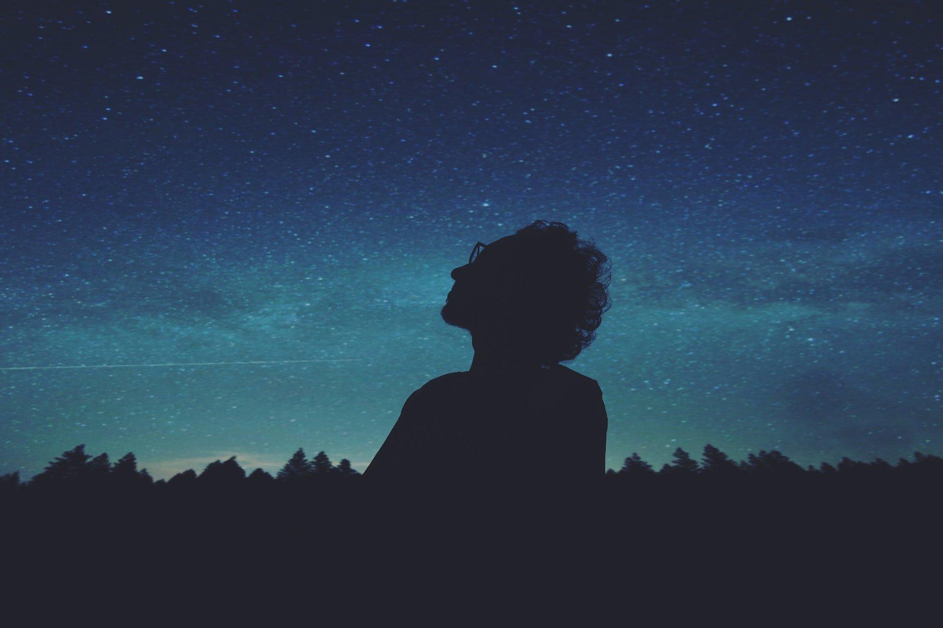 Silhueta de pessoal num céu estrelado.
