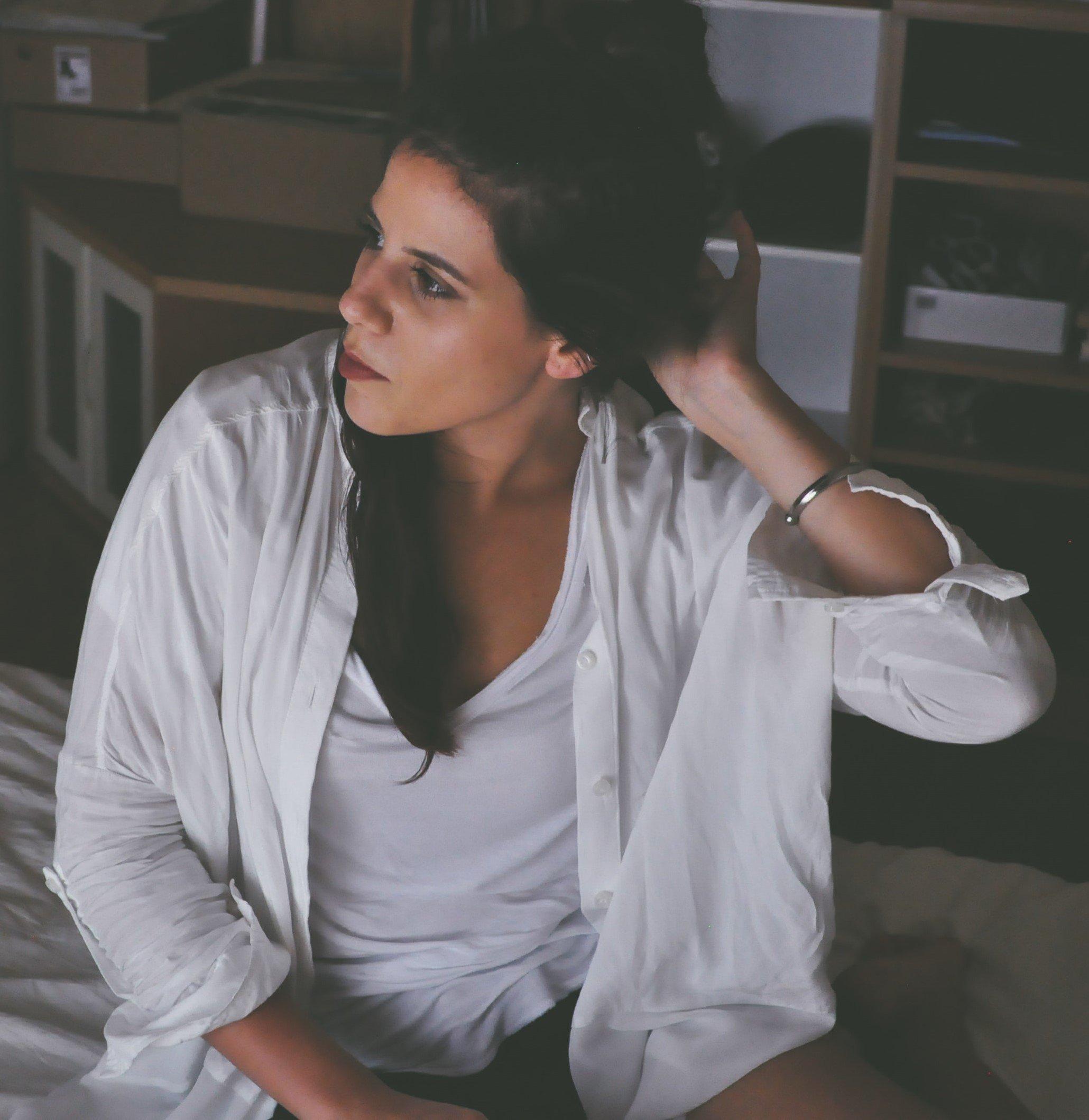 Mulher sentada na cama olhando para o lado