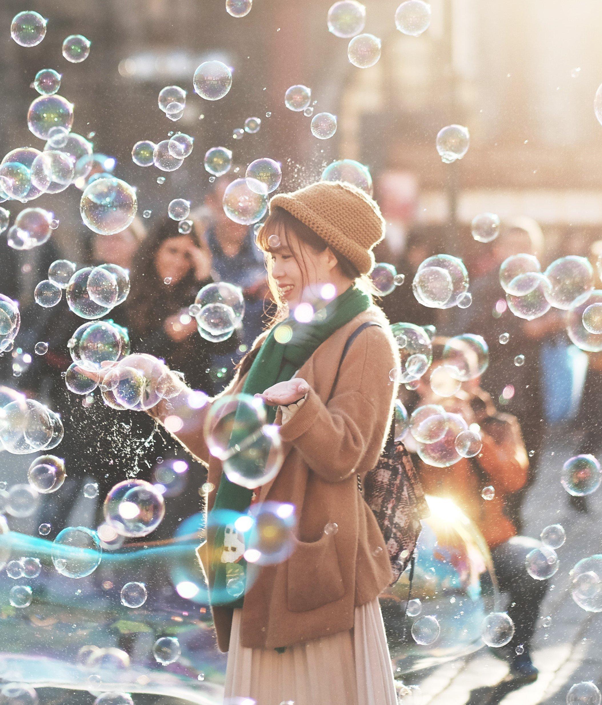 Mulher no meio da rua com bolhas de sabão e pessoas ao seu redor
