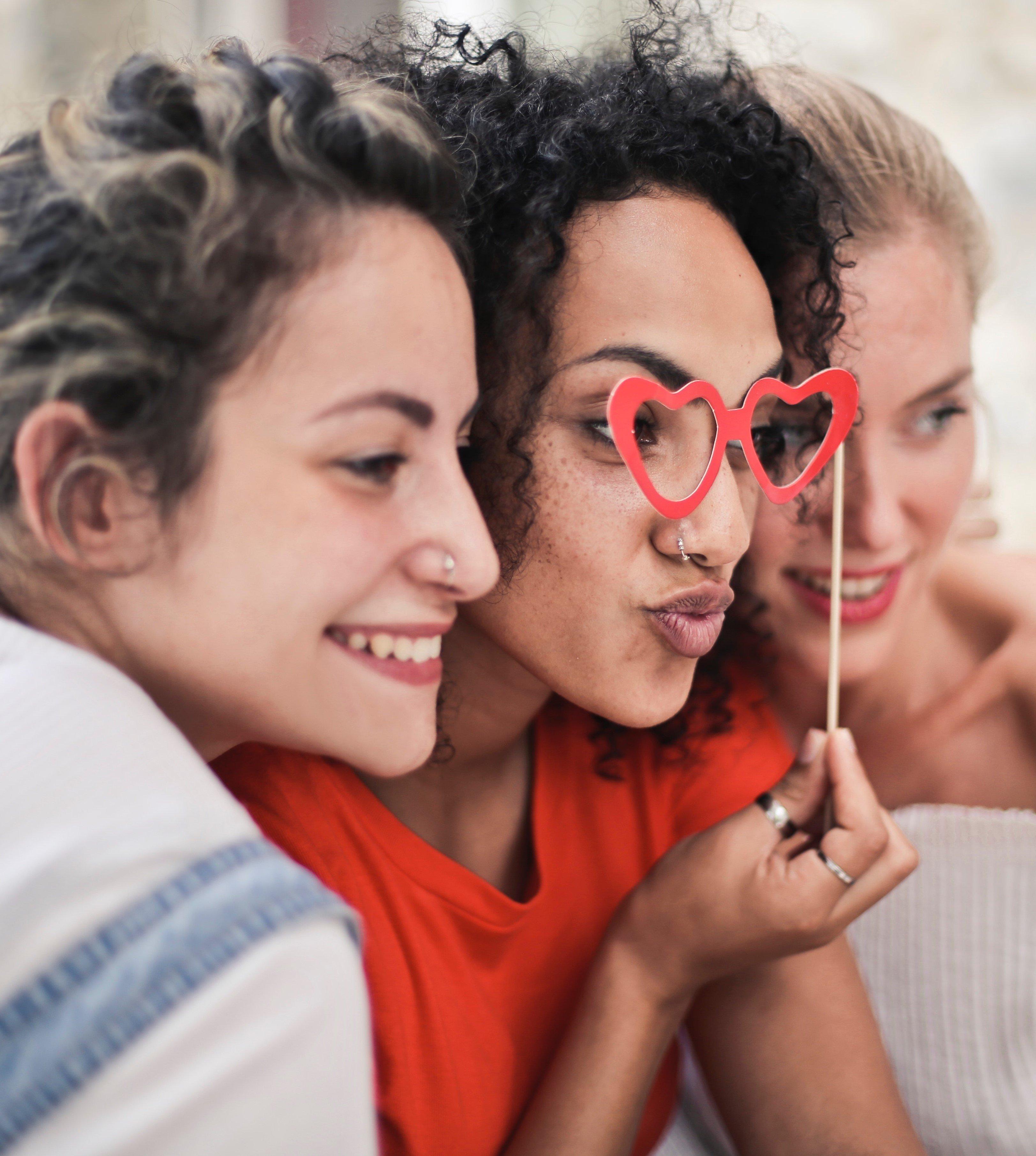 Três mulheres de lado sorrindo