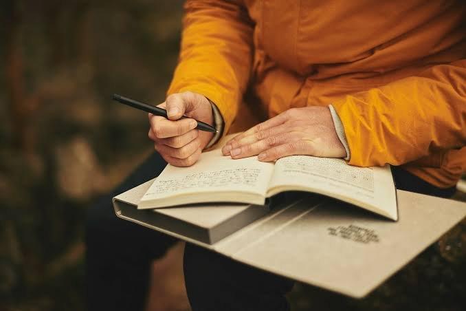 Foto de mulher corrigindo livro