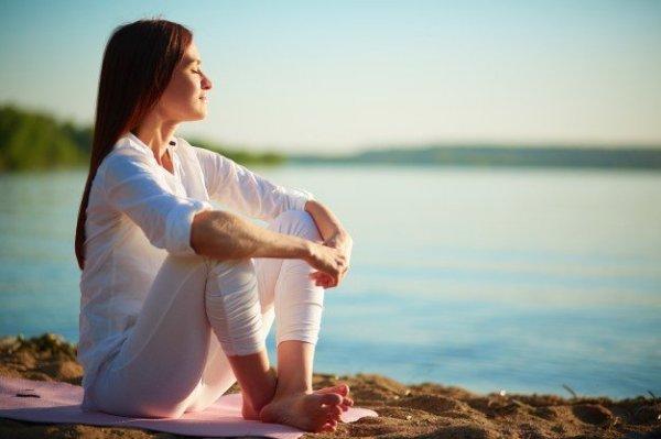 Mulher sorrindo com os olhos fechados sentada ao lado de um lago.