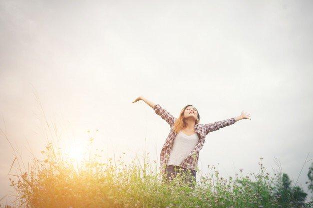 Mulher sorrindo com os braços abertos para cima.