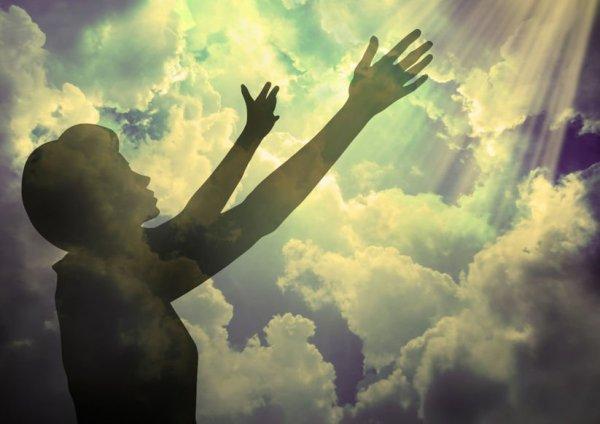 Silhueta de mulher com os braços estendidos ao céu.