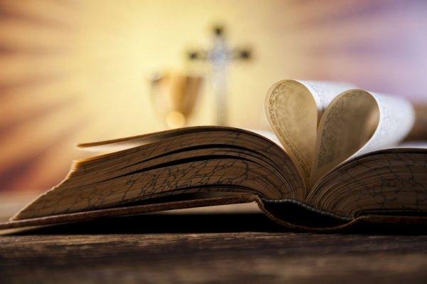 Duas páginas da bíblia formando um coração ao dobrar.