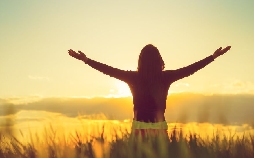 Mulher olhando para o horizonte com os braços para o alto.