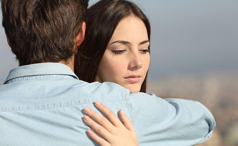 Mulher com olhar distante enquanto recebe abraço