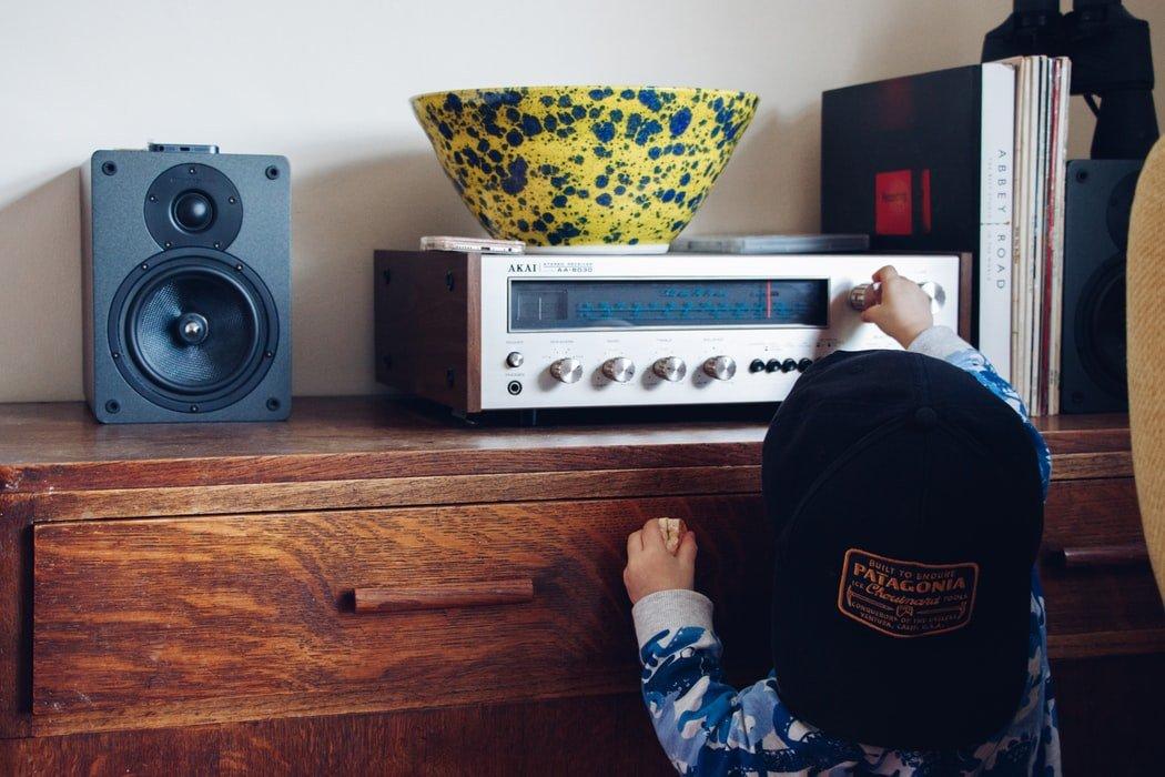 Criança se esticando para girar botão que troca de estação de rádio em aparelho que fica em cima de uma estante.