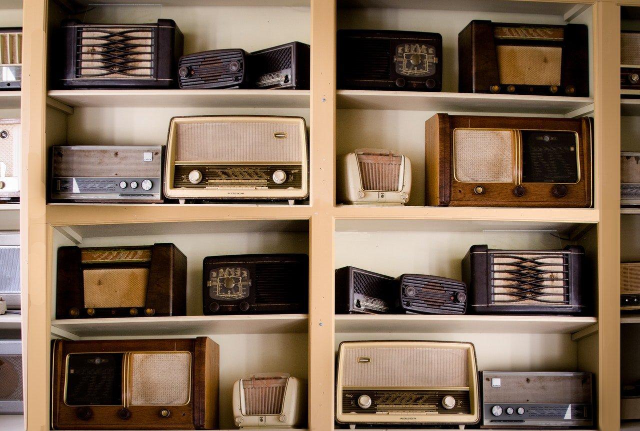 Estante com oito prateleiras, e dois rádios antigos em cada, de diversos modelos diferentes.