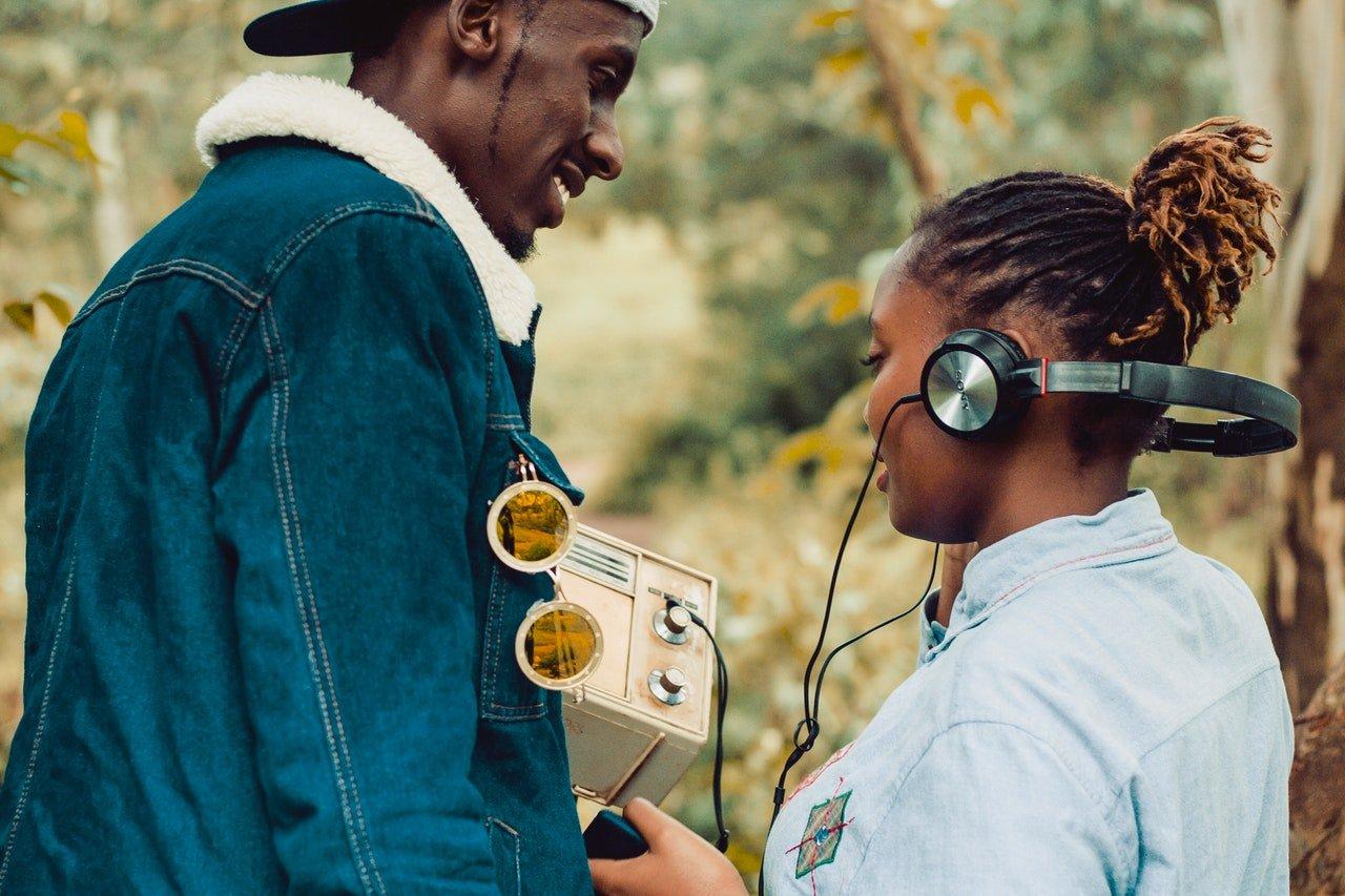 Homem segurando rádio antigo e sorrindo para mulher, que usa fones de ouvido ligados ao rádio.