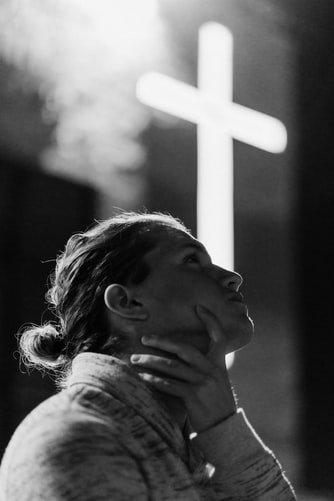 Mulher pensativa com cruz ao fundo